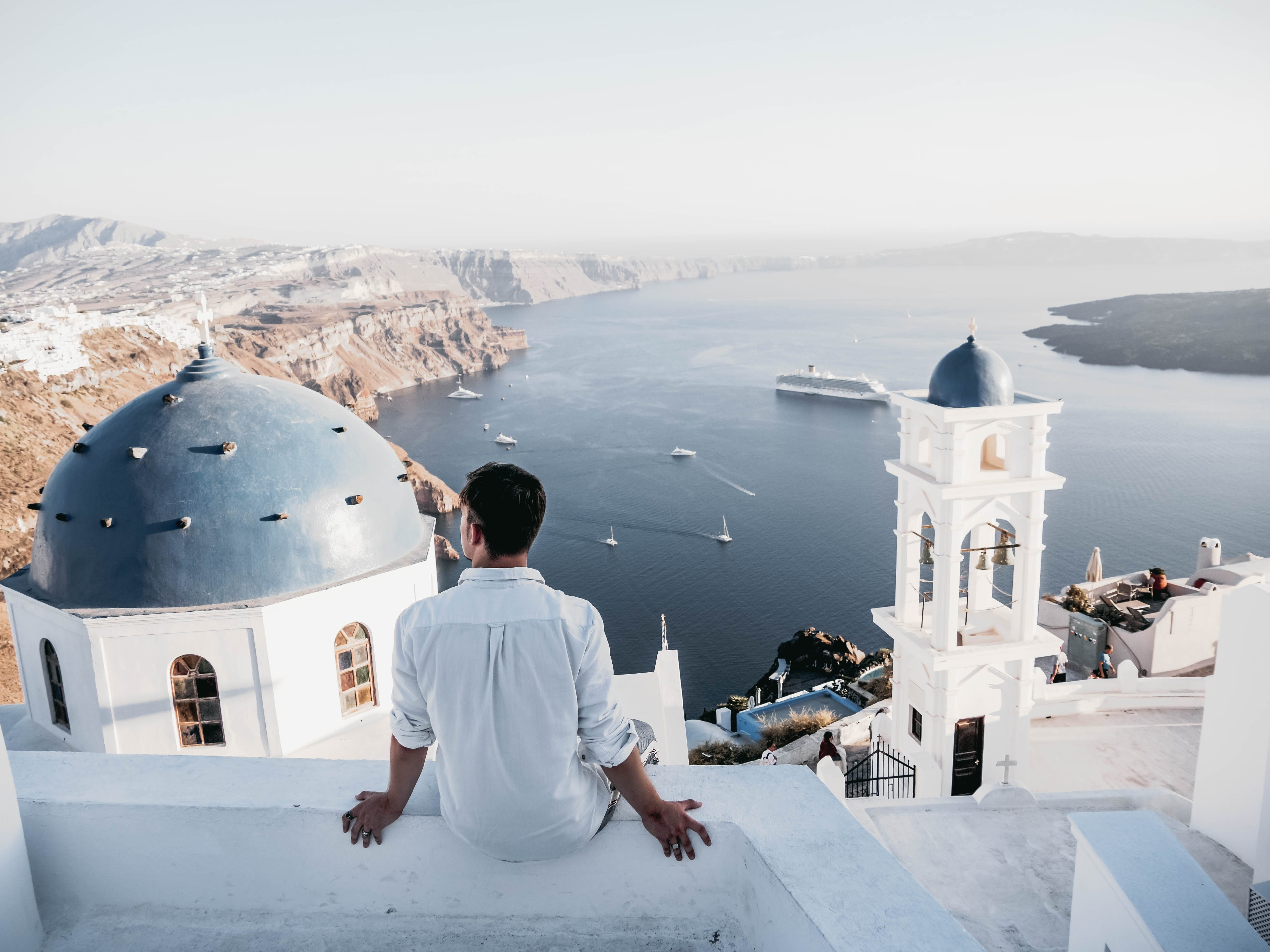 greece - man sitting on edge looking over water