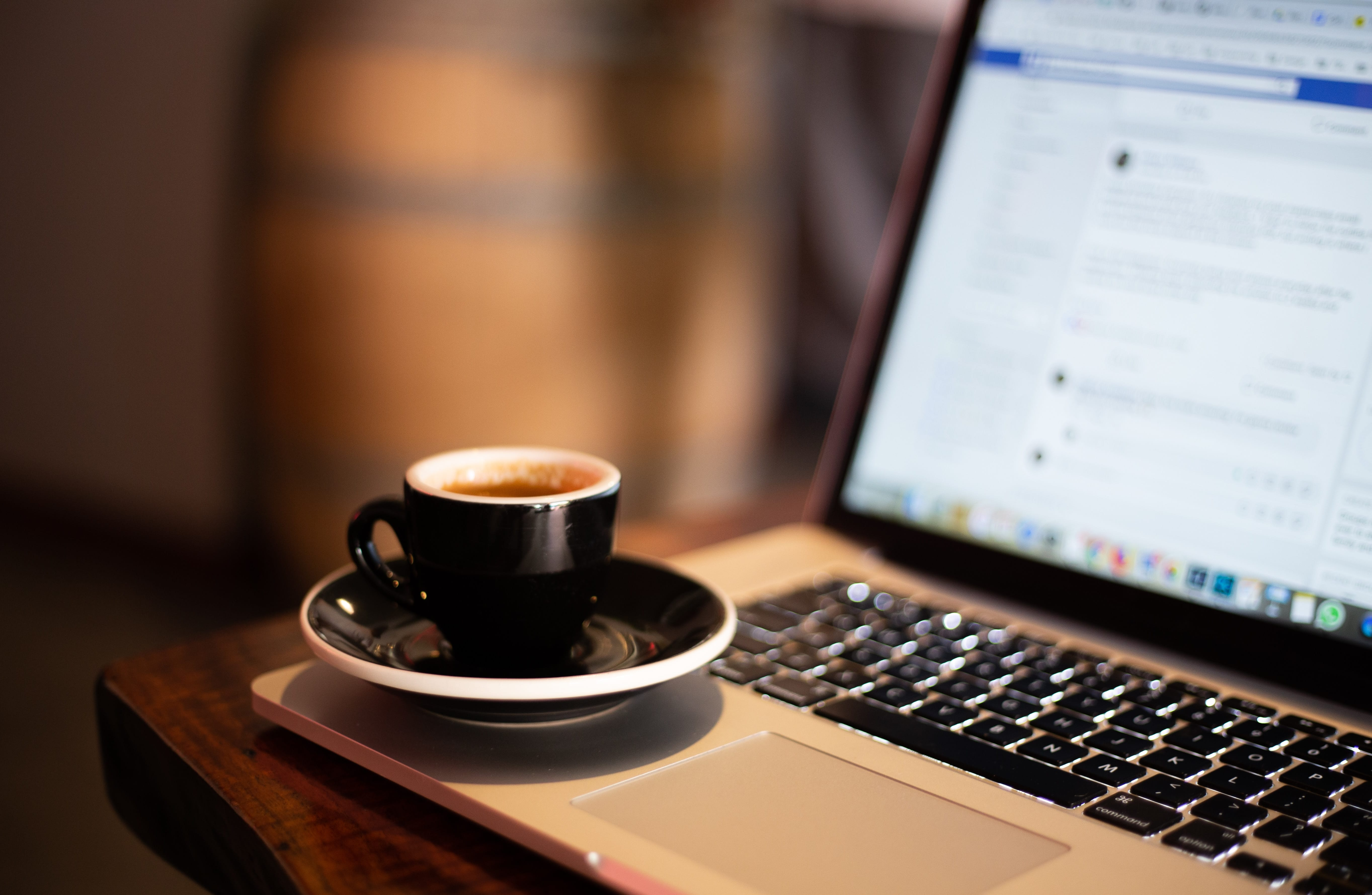 black coffee mug on laptop with facebook on screen
